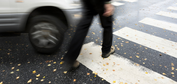 Man on pedestrian crossing in autumn in danger of being hit by car ** Note: Slight blurriness, best at smaller sizes