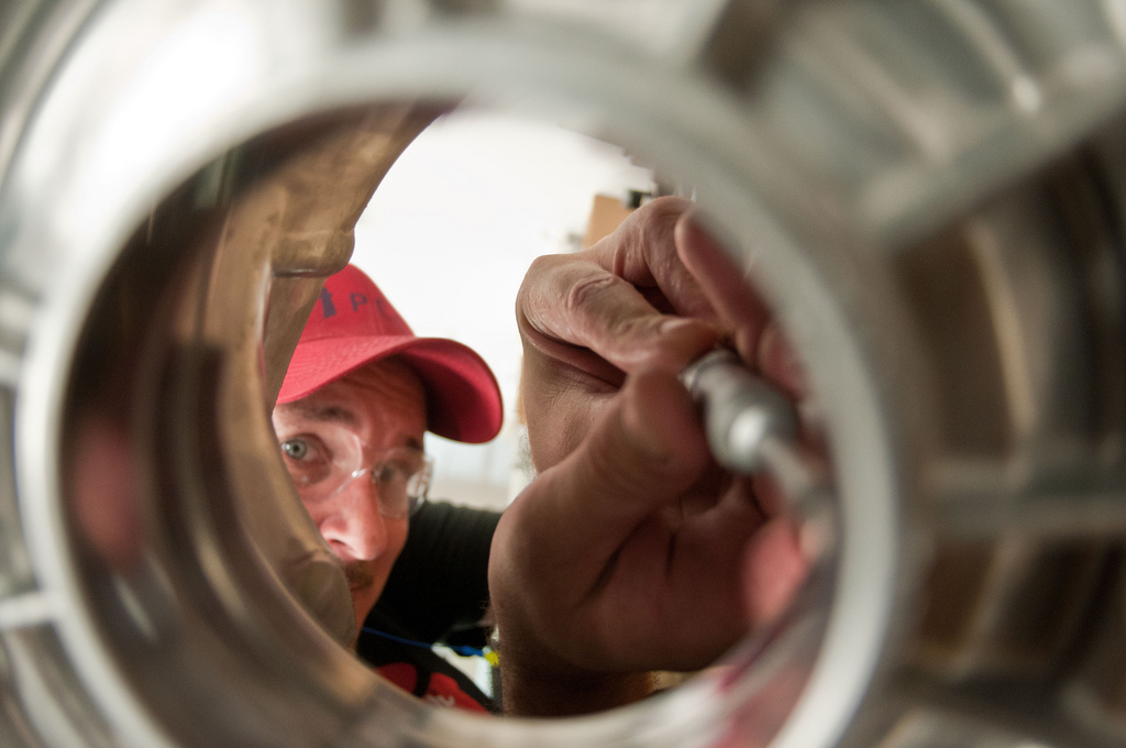 """Quality Control Specialist Tim Russell uses a specialized micrometer to measure of machining performed at Port City Group's Port City Castings Corporation manufactures high-pressure aluminum die-castings, mostly for the automotive industry, in Muskegon, MI, facility on Wednesday July 20, 2011. Port City Group boosted its employment by 12 percent over last year thanks to two Rural Business Guaranteed Loans totaling $9.6 million. In its 80,000 sq. ft. facility, machines that range from 800 – 1,600 tons, and cast A380 aluminum alloy products from melted ingots of aluminum, into automotive components of U.S.A. made vehicles. The process features a variety of robotic presses; computer controlled machining; quality control facility; and complete measurement and testing laboratory. In 2009 banks were backing out of loans for PCG equipment purchase agreements. The U.S. Department of Agriculture (USDA) loan guarantee helped make the loan possible with its guarantee. PCG obtained the needed robotic and other equipment. This resulted in a stable workforce that has since grown. When asked about their USDA experience, Port City Group Sales Manager Laura LaGuire said, """"It was great! They were very helpful. Everything that came up was handled smoothly, the money came in place when it was needed, and it was a very smooth transition."""" USDA Photo by Lance Cheung."""